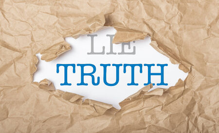 Truth and lie words on white paper with copy space and torn cardbox