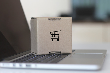 Online shopping cart concept with laptop and cardboard box