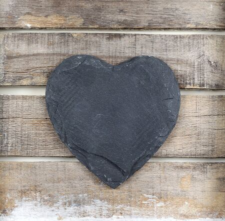 Stone heart on old  wooden background Archivio Fotografico