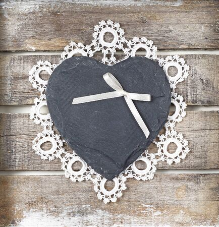 Stone heart with ribbon and lace on wooden background