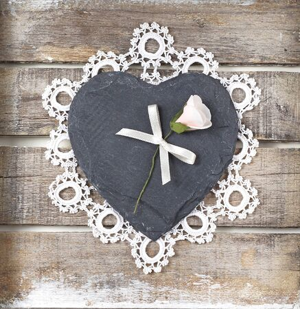 Stone heart with rose on old wooden background