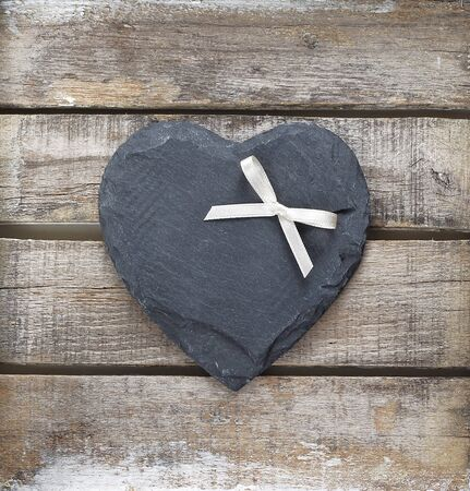 Stone heart and ribbon on old wooden background