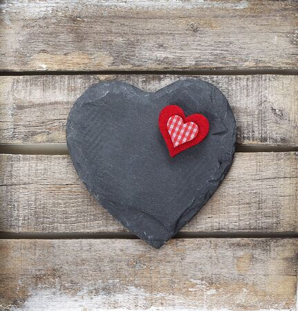 Stone heart on old wooden background