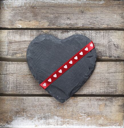 Stone heart and ribbon on wooden background