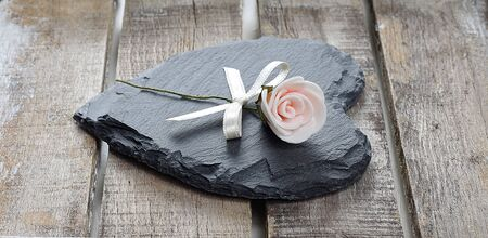 Stone heart and rose on old wooden background Stock Photo