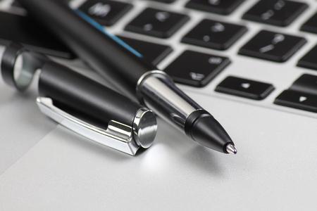 Black ballpoint pen on computer keyboard closeup