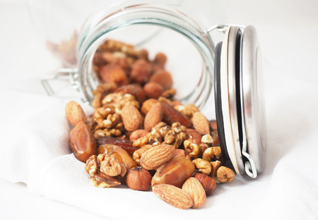 Glass jar of mixed nuts on white background Archivio Fotografico
