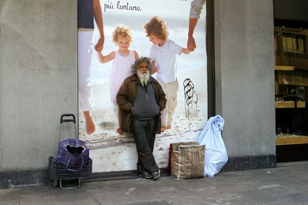 Milan, Italy - April 21, 2012: Homeless with their belongings stands at the poster with the image of the family.
