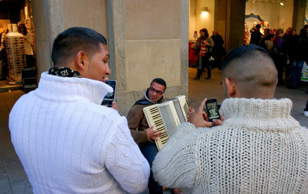 take a history: Munich, Germany - October 22 2011: Street musician, accordion playing evening. To listen to him and take pictures of the audience.