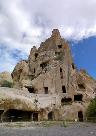 cave house: Cappadocia. Turkey. Cave house in the natural erosion formations.. Amazing Cappadocia Rocks on the background of clouds Stock Photo