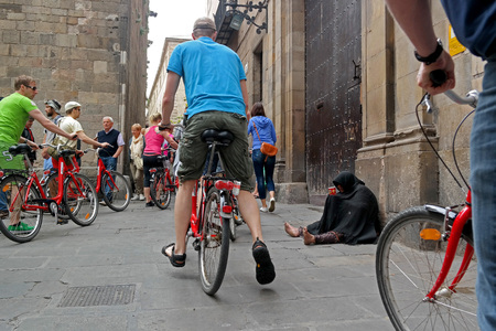 social outcast: Barcelona, Spain - May 17, 2014: Beggar dressed in black sitting in the street of the Gothic Quarter. A group of tourists on bikes toured it.