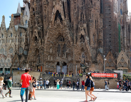 catalunia: Barcelona, Spain - May 17, 2014: Tourists walk from the Sagrada Familia - the creation of the great architect Antoni Gaudi.