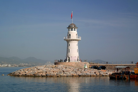 migrated: Lighthouse in the port of Alanya, Turkey. The lighthouse was established in Paris in 1880, then was dismantled and then migrated to the Turkish coast in Alanya. Stock Photo