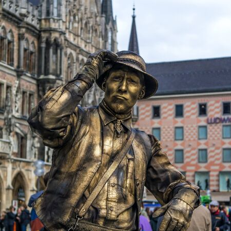 earns: Munich, Germany - April 13, 2013: street pantomime at the marienplatz in Munich earns money as a typical bavarian rural old person. The actor welcomes the audience.