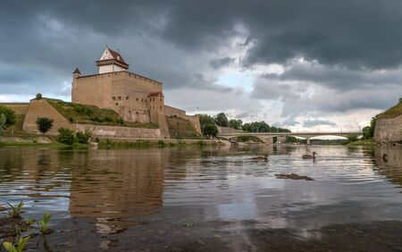 herman: Narva Castle in Estonia on the background of a stormy sky. Ducks swimming on the background of bridge.