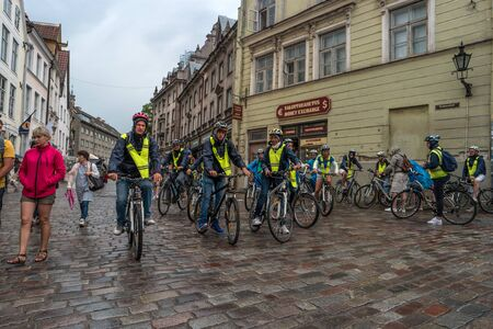 reflective: Tallinn, Estonia - July 30, 2015: biking tour passes through the streets of Tallinn. Tourists equipped with helmets and reflective zheltvmi zhtletami. It is raining outside.