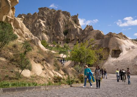 goreme: Cappadocia, Turkey - April 29, 2014: Tourists visiting Cave Church at Goreme in Nevsehir. There are more than 10 cave churches in Goreme Open Air Museum. They form the largest monastery complex carved into the rock formations. Editorial