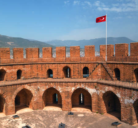 upper floor: Alanya Castle. The upper floor of the Red Tower from a red brick with a Turkish flag and the blue sky.