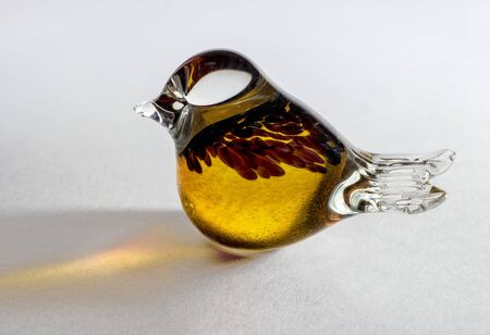 soldered: Glass statuette of a bird. Yellow glass soldered with additional decorative elements. A figurine on a white background, the light is reflected on the background. Bird as a great bird.