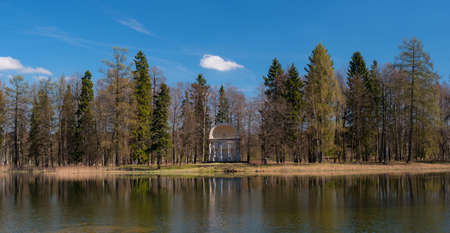orla: St. Petersburg, Gatchina Park, Pavilion of Eagle Island at White Lake. Trees and the pavilion reflected in the water.