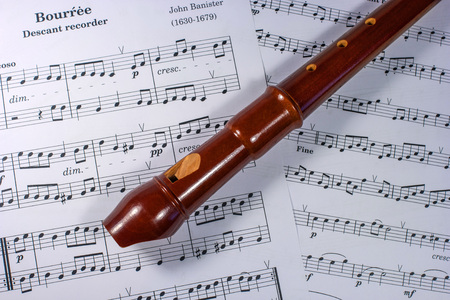 flute key: Soprano block flute lies on a music sheet. The tool is made of boxwood, pear, plum ...