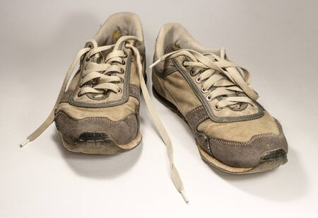 frequent: Old sneakers on a light background. Trainers worn frequent use. Stock Photo