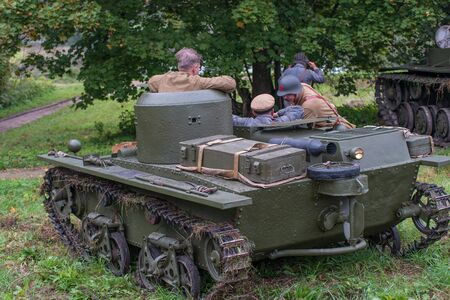 ambush: Gatchina, Russia - September 11, 2016: The historical reconstruction of World War II. Lightweight floating tank T-37A. The tank is in ambush, commanders are discussing a plan of action.