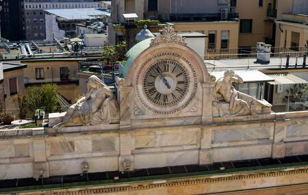 third world: Milan, Italy - April 21, 2012: The clock with sculptures on facade of building seen from Milan Duomos rooftop. The Milan Cathedral is the second largest church in Italy and the third in the world. Editorial