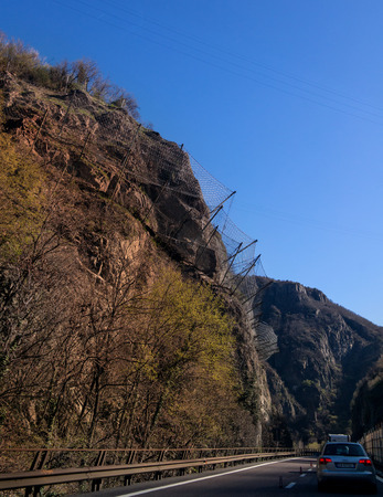 rockslide: Protection wire mesh against falling rocks from the mountains. On the mountain road going car. Stock Photo