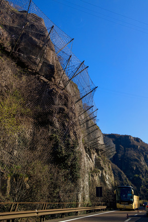 rockslide: Protection wire mesh against falling rocks from the mountains. Bus rides on a mountain road. Stock Photo