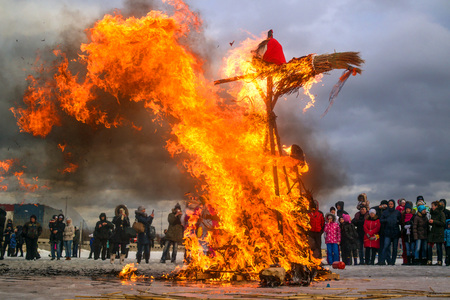 Saint-Petersburg, Russia - February 22, 2015: Feast Maslenitsa on Vasilyevsky Island. Burning doll - the flames destroyed almost the entire doll. Spectators take pictures of what is happening. Editorial