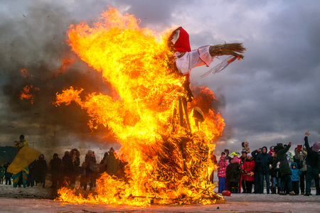 enjoyed: Saint-Petersburg, Russia - February 22, 2015: Feast Maslenitsa on Vasilyevsky Island. Burning doll - the flames destroyed almost the entire doll. The audience enjoyed the holiday.