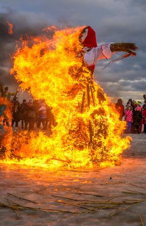 Saint-Petersburg, Russia - February 22, 2015: Feast Maslenitsa on Vasilyevsky Island. Burning doll - the flame is reflected on the snow. Spectators watch the scene.