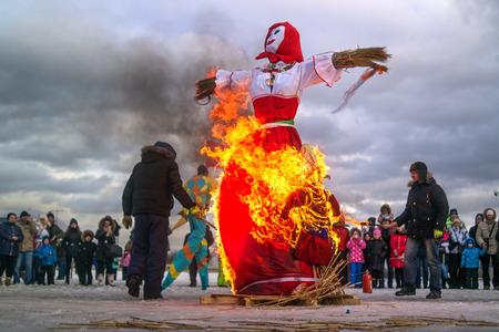 heathen: Saint-Petersburg, Russia - February 22, 2015: Feast Maslenitsa on Vasilyevsky Island. Burning doll - a doll set fire to the organizers. Flame lights up on the skirt. Editorial