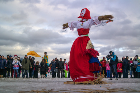 muñecas rusas: Saint-Petersburg, Russia - February 22, 2015: Feast Maslenitsa on Vasilyevsky Island. Burning doll - a doll has been prepared, the audience are at a safe distance.