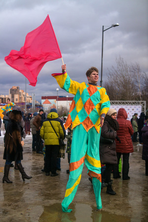buffoon: Saint-Petersburg, Russia - February 22, 2015: Feast Maslenitsa on Vasilyevsky Island. Buffoon with a flag on stilts and calls people to the feast.