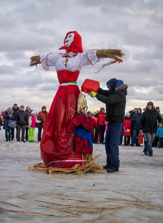 Saint-Petersburg, Russia - February 22, 2015: Feast Maslenitsa on Vasilyevsky Island. Burning doll - a doll ready, organizers Doll pour flammable liquid. Editorial