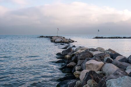 yacht club: Stone jetty in the early morning. Breakwater protects the waters from the waves yacht club. Stock Photo