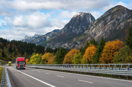 Red truck driving on the highway in the Alps. View of the mountains and yellow autumn trees. Stock Photo