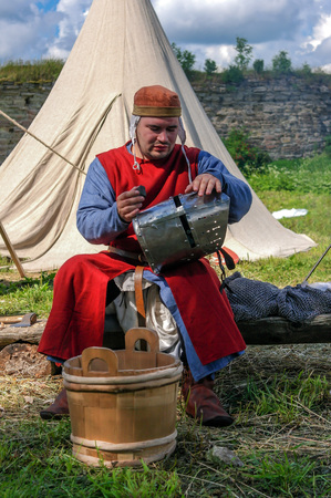 knightly: Koporje, Leningrad region, Russia - July 21, 2012: Reconstruction of knightly duels and battle chivalrous life camp. Knight prepares to battle its ammunition. Editorial