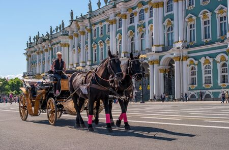 Saint Petersburg, Russia - June 17, 2017: Horse carriage carries tourists on the Palace square along the Hermitage.
