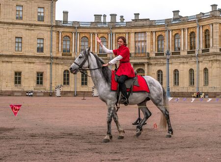Gatchina, St. Petersburg, Russia - September 30, 2017: Horse show of Cossacks on the parade ground of the Gatchina Palace. A Cossack girl on a white horse welcomes the audience.