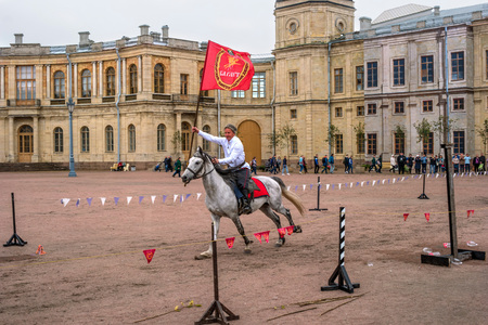 Gatchina, St. Petersburg, Russia - September 30, 2017: Horse show of Cossacks on the parade ground of the Gatchina Palace. A Cossack in a white shirt jumps with a red flag.