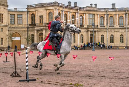 Gatchina, St. Petersburg, Russia - September 30, 2017: Horse show of Cossacks on the parade ground of the Gatchina Palace. The Cossack rides with a sword.