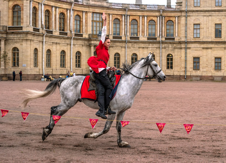Gatchina, St. Petersburg, Russia - September 30, 2017: Horse show of Cossacks on the parade ground of the Gatchina Palace. . Young Cossack performs tricks on horseback.