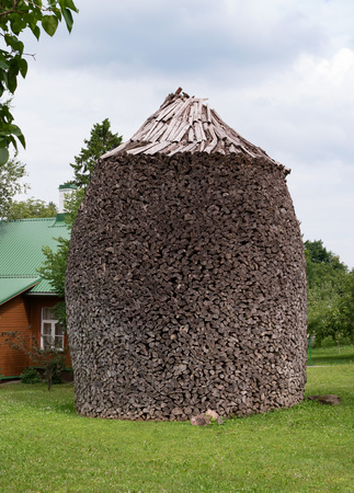 The Puhtitsa Dormition convent. Kuremae, Estonia. Baltic country. Woodpile. Firewood is laid in the form of stacks. The original masonry wood Imagens - 106305981