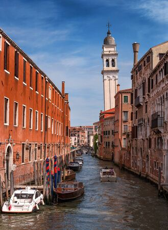 Venice, Italy - May 07, 2018: View of Venice canal. On the left is the police station. Ahead vinda inclined bell tower of the Church of St. George of the Greek Cathedral. Venice. Italy