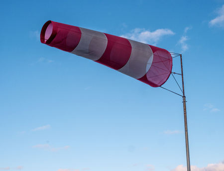 Windsock during a strong wind. Windsock shows wind direction and strength. Made of fabric in the form of a cone. It is installed at the airports of small aircraft or on the basis of sailing ships.