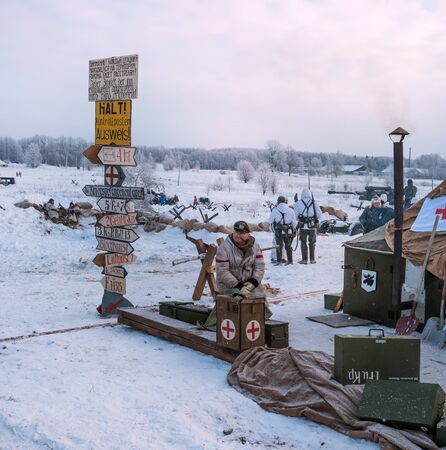 Krasnoye Selo, St. Petersburg, Russia - January 19, 2019: Military historical reconstruction - the battle for Leningrad. Military field hospital of the German army. Medical orderly smoking a pipe. Editorial