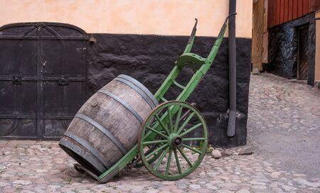 Trolley for transporting wooden barrels. Wooden barrel on a trolley. Old cart. Old barrel.